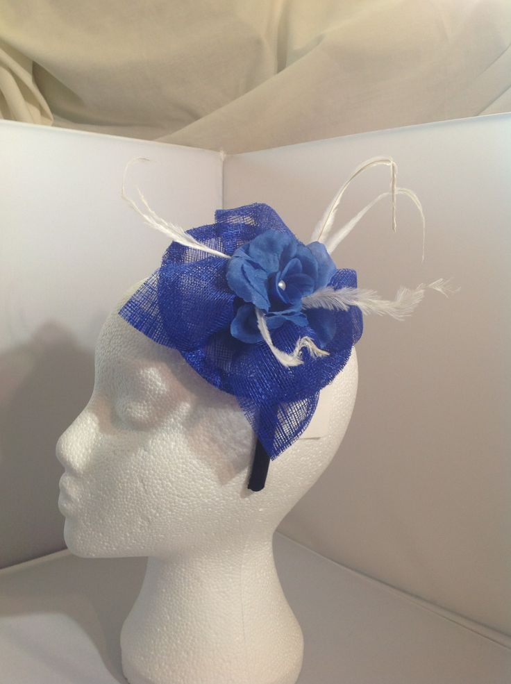 The Minnie is a small fascinator on a black head band the base is sapphire sinamay with a centre piece of a pearl detailed sapphire flower surrounded by sapphire sinamay leaves and diamond white flowers to finish.$75 AUD.