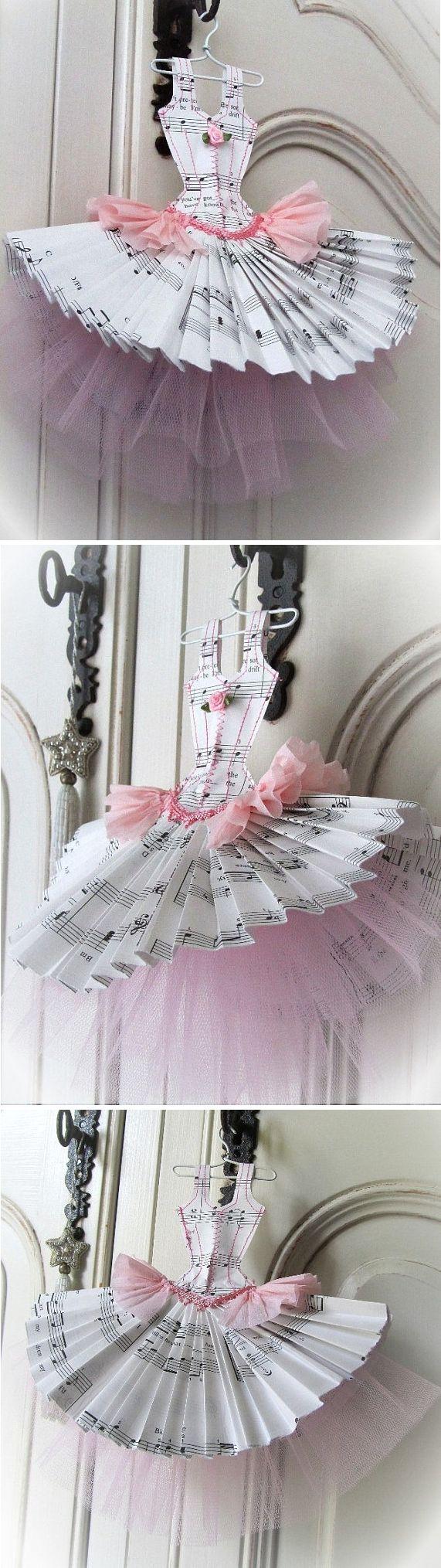 """Robe faite à partir de papier """"musique"""", de papier crépon et de tulle. Elle est cousue avec du fil de coton rose et est garnie d'un galon et d'une fleur. Elle mesure 23 cm de hauteur x 27 cm de largeur et est livrée avec son petit cintre blanc."""