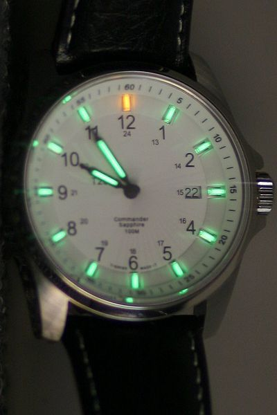 Swiss Military Watch Commander model with tritium-illuminated face | Tritium a radioactive isotope of hydrogen with half-life of 12.32 years that emits very low-energy beta radiation. It is used on wristwatch faces, gun sights, and emergency exit signs. The tritium gas is contained in a small glass tube, coated with a phosphor on the inside. Beta particles emitted by the tritium strike the phosphor coating and cause it to fluoresce, emitting light, usually yellow-green.