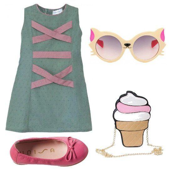 Un bellissimo abito di cotone, stile anni '69, verde con nastri rosa, è abbinato a ballerine di pelle rosa, borsa a tracolla a forma di cupcake, occhiali a forma di gatto.