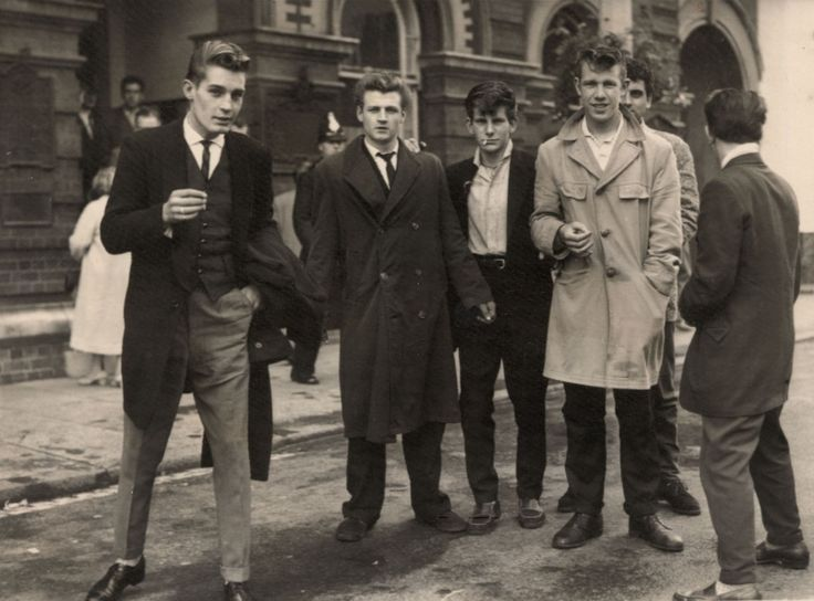 "This photograph is of ""Teddy Boys,"" which was known as the UK's first subcultural style after the war. These boys donned Edwardian inspired dress, consisting of drainpipe trousers, a narrow bowtie, and shoes with thick soles. They also had Brilliantined hair, shaped into a DA( or duck's ass). The Teddy Boy was a very obvious, known look during the decade."