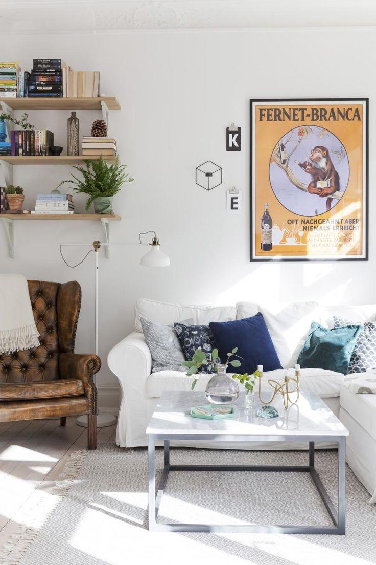 TRENDY STUE: I den lyse stuen står en sofa fra Ikea. Salongbordet er hjemmelaget, stolen fra auksjon, gulvlampen fra Ikea, den innrammede plakaten bestilt fra USA, og vegghyllene fra Norrgavel. En hjørnesofa gir mye sitteplass uten å ta for mye av rommet. Det store møbelet lettes opp av et bord med slanke bein og stilren design.   Foto: Karin Johansson