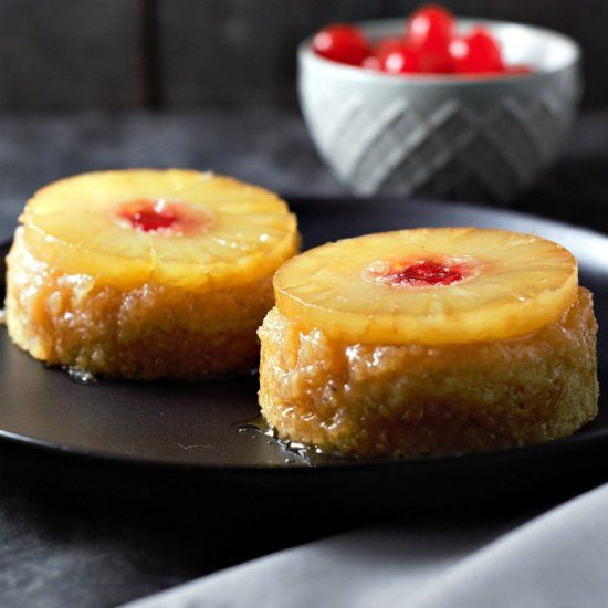 Individual Pineapple Upside-down Cakes have moist yellow cakes topped with pineapple, maraschino cherries, and brown sugar.