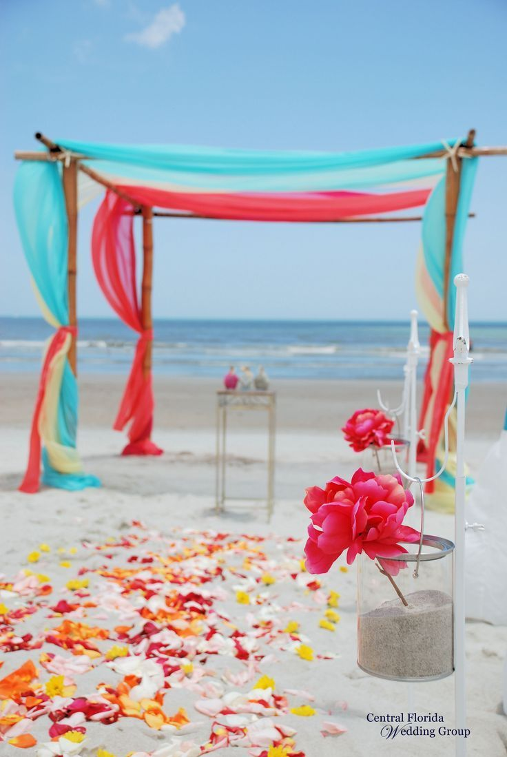 Tropical beach wedding, 4-post bamboo with turquoise, yellow, coral, and hot pink sheers, turquoise chair sashes, vases along the aisle, & flower petal aisle