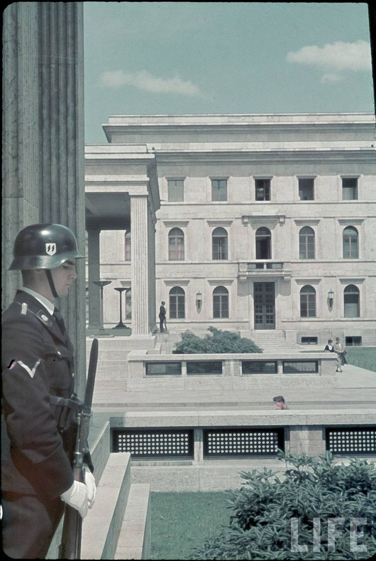 An SS-Allgemeine Honor Guard maintains his post outside the Führerbau on the Königsplatz in Munich. The Führerbau was an official diplomatic building built in 1937 by Paul Ludwig Troost who utilized Hitler's preferred neo-classical/neo-Greek architectural design. Most notably, the building was the site of the signing of the Munich Agreement of 1938 between Adolf Hitler and British Prime Minister Neville Chamberlin which permitted the German majority-populated Sudetenland, then part of…