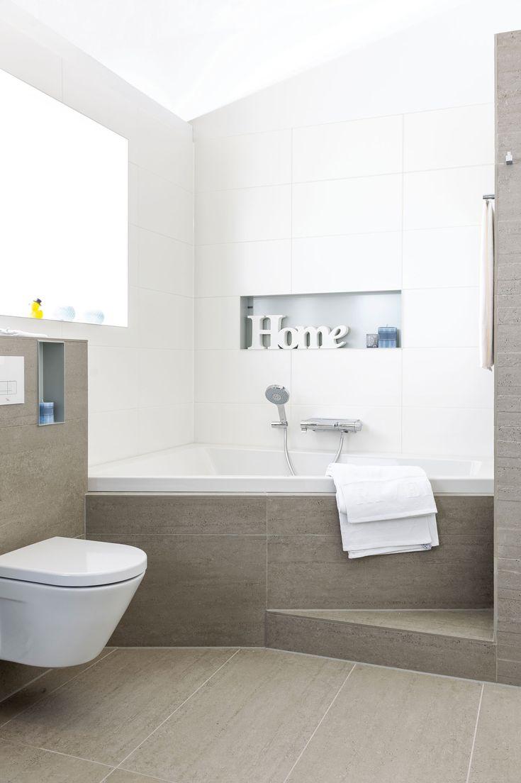 In deze badkamer voelt u zich al snel thuis. Aardetinten en strakke witte tegels worden gecombineerd. Nissen om praktisch of gezellig in te richten.