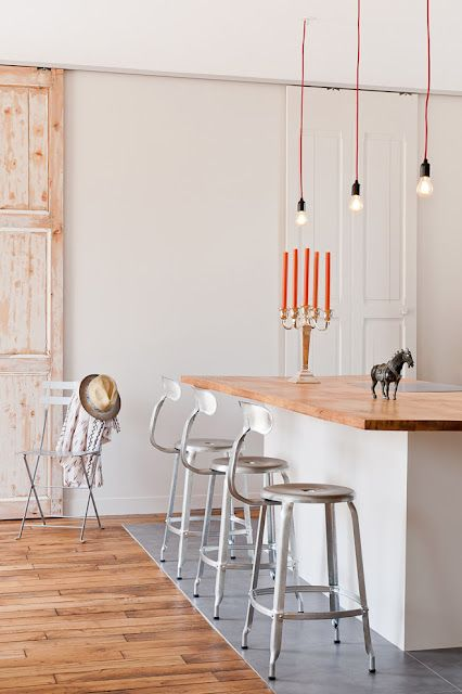 Muriel lives in Porte de St Ouen, Paris. She remodeled an old apartment into a light filled open space loft. Walls have been painted white, oak floors sanded, color accents added throughout the flat. What a lovely and welcoming interior!