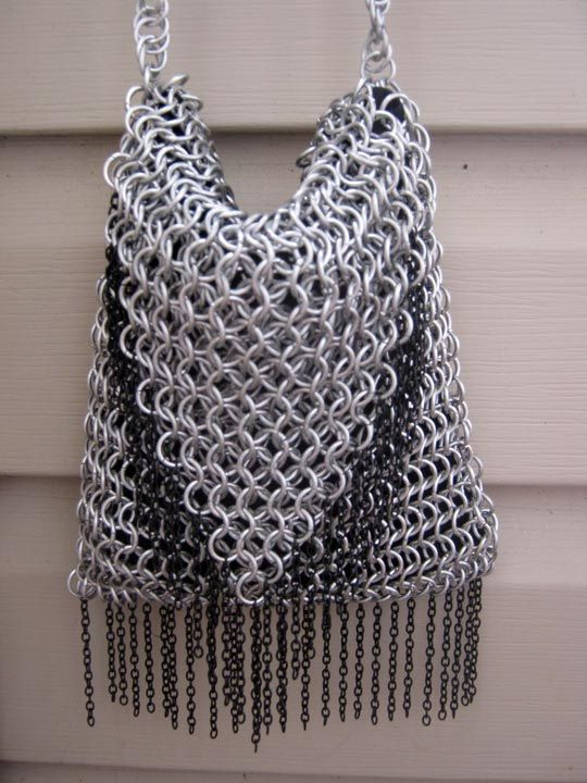 This purse is made from 16 gauge 5/16ths inch bright aluminum rings, black chains, and black satin-like lining. The strap is woven in spiral