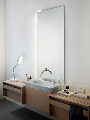 Note the simplicity of the faucet floating out of the mirror and simple lines throughout the design.