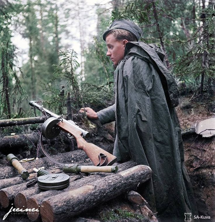 An exhausted Finnish soldier armed with his Suomi KP Suomi-konepistooli (sub machine gun) and a supply of hand grenades, on duty at an outpost during the 'Continuation War' 1944.