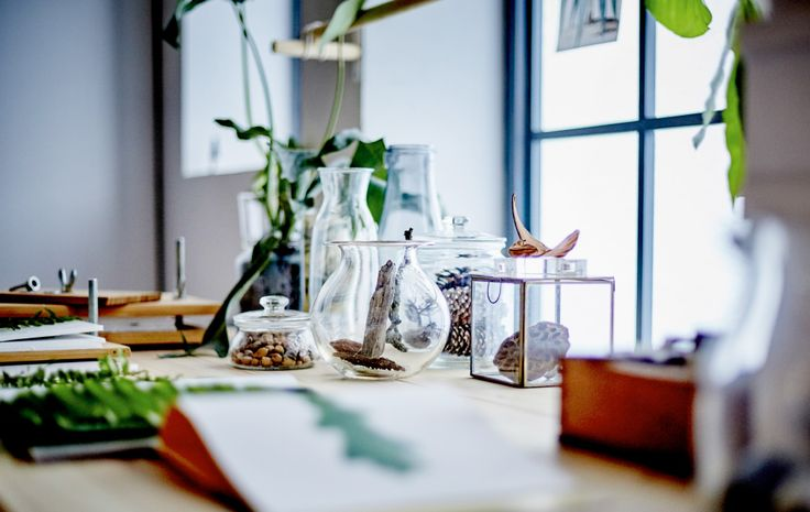 A close-up image of a desk in front of a window, decorated with botanical elements. --I always have little odds and trinkets like this, so I dig this idea.