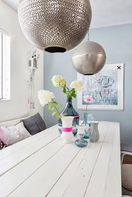 Méchant Design: a neon touch. Love the round metallic chandeliers over a simple wood table. Mixing styles. Eclectic.