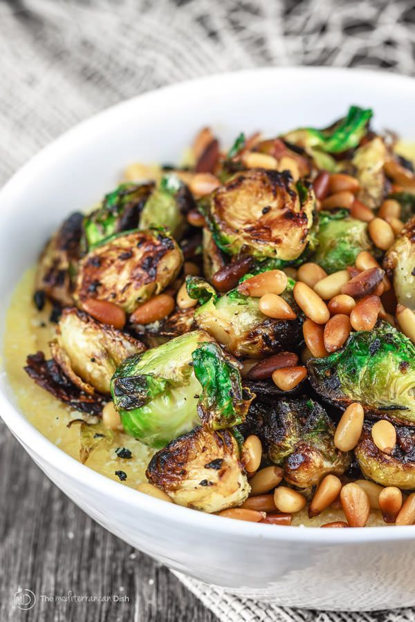 A Mediterranean-style brussel sprouts recipe; fried in olive oil with onions and served with quick Parmesan polenta and pine nuts. Side dish in 20 minutes!