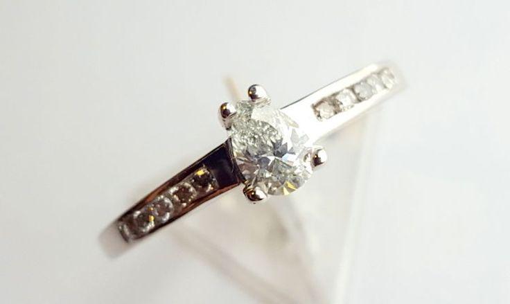 Pierścionek białego złota pr. 0,585 z diamentem w kształcie łzy i brylantami.
