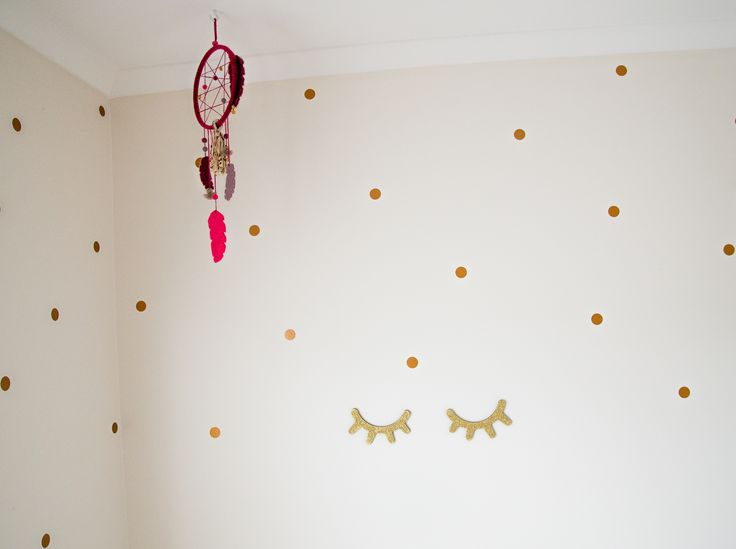 Stunning girls room, copper polka dot wall stickers with gold glitter sleepy eyes and vibrant pink dream catcher, creates such a feeling of wonder.  Styling by Little Nook Interiors