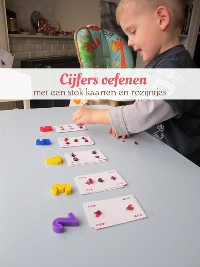 Op een speelse manier de getallen en aantallen leren aan een peuter met een stok kaarten, rozijntjes en nummermagneten.