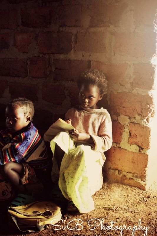 A small girl practices printing while her younger sibling waits for her lesson just inside the doorway of the school in Maranatha
