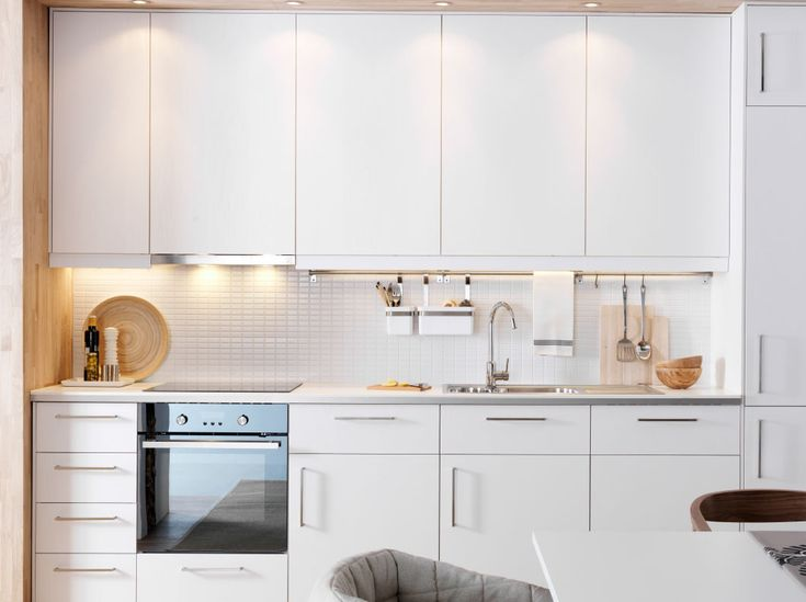 Moderna cocina blanca con frentes RÅSDAL, encimeras blancas y electrodomésticos integrados