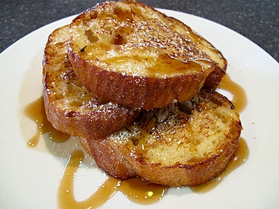Eggnog French Toast  Instructions: Cut up a loaf of crusty french or sourdough bread into thick slices. Then take slices and dip both sides in eggnog (no egg or milk needed). Toss in a pan with lots of butter and cook till golden brown. Serve with powdered sugar, Aunt Jemima and a slab of bacon. Mmm, Mmm good.