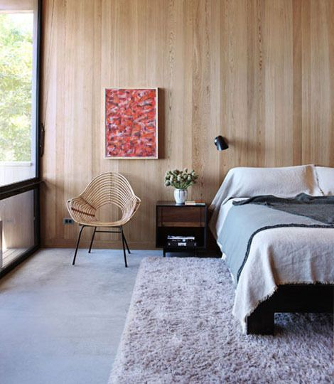 Similar to our room. Concrete floor, vertical grain oak wood paneling on wall behind bet.