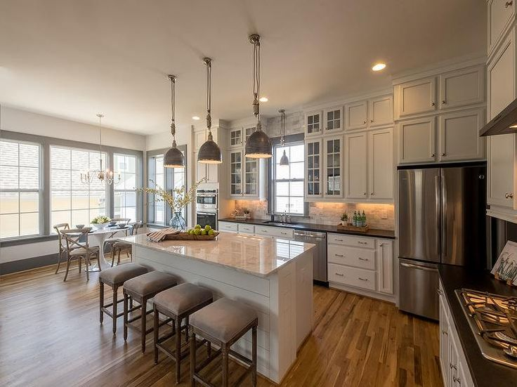 Industrial pendants hang over a white shiplap island finished with a white marble countertop seating four backless gray French bar stools facing a gray trimmed window fixed above the kitchen sink and placed between glass front cabinets fixed above gray marble subway tiles complementing white cabinets topped with black quartz countertops as a stainless steel fridge sits under two row of cabinets adorning polished nickel knobs in this gorgeous l-shaped kitchen.