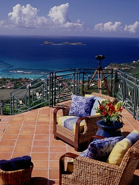 Armchairs take in the scene. The northwest-facing setup puts them in position for sunset viewing. The property, on one of St. Barth's highest peaks, captures postcard vistas of azure waters, distant islands, and cruising watercraft