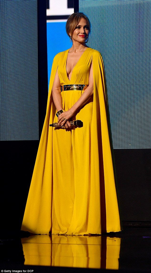 Ray of sunshine: J.Lo looked stunning in a bright yellow jumpsuit with dramatic cape sleev...