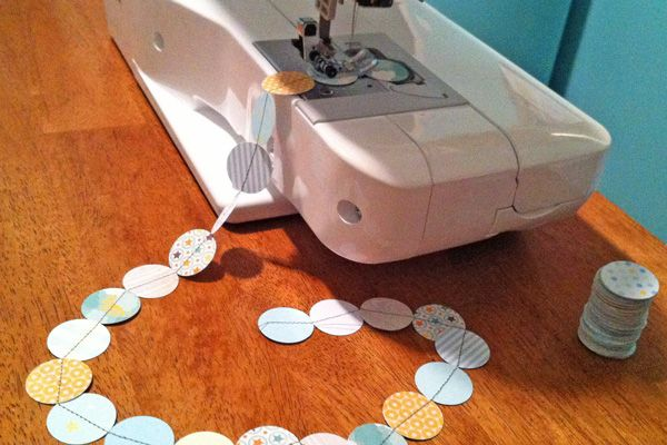 Sewing a garland made up of scraps/pieces of scrapbook paper ... I like the circles, but it would work with so many different shapes!
