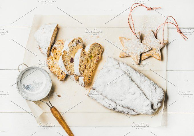 #German Christmas cake Stollen  Traditional German Christmas cake Stollen cut in pieces with festive gingerbread star shaped cookies on white background top view horizontal composition