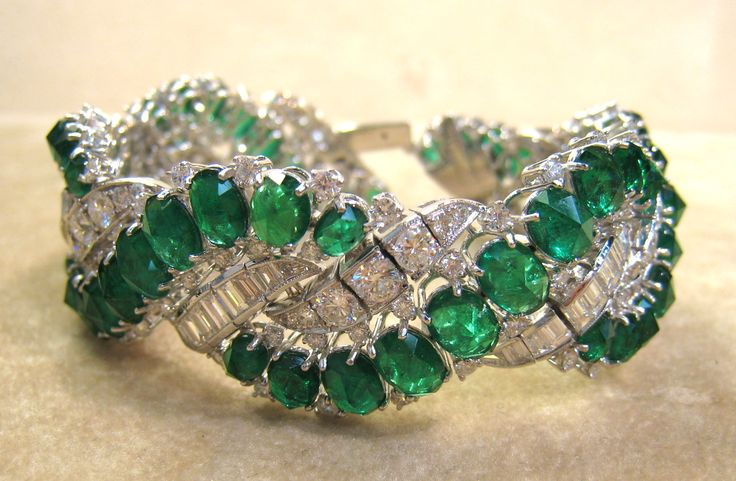 Emerald & Diamond Bracelet - This beautiful bracelet is all hand made in platinum, set with 31.92 carats of fine clean Colombian emeralds along with 11.96 carats of high quality diamonds. The diamonds are all G+ color & VS+ clarity, approx one inch wide.