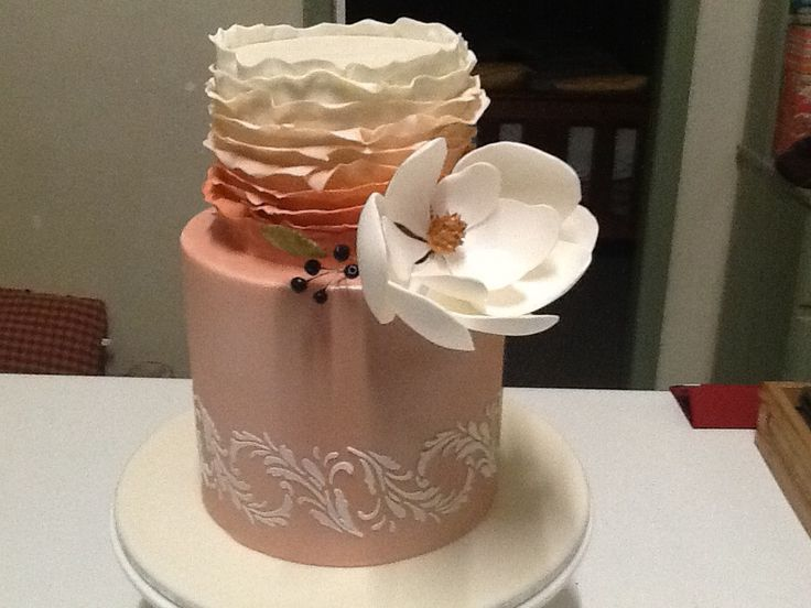 Two tiered stencilled and ruffled cake with large Magnolia