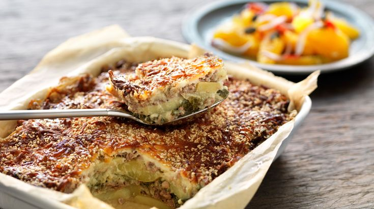 Oksekød bagt i lag med kartofler, grønkål og sesam