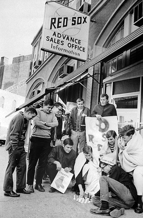 Red Sox fans bundle up and play chess while waiting in line for tickets to the 1967 World Series.  Photographed by: Bettmann/CORBIS