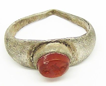 This is an ancient Roman silver intaglio ring, dating to the 1st - 2nd century A.D. The ring is intact with its original carnelian intaglio depicting a cockerel (rooster) chasing a rodent, with its tail in his beak. Such scenes would have been familiar around most rural areas where the mice and rats would have been eating the stored grain. The cockerel was representative of Mercury, god of trade, commerce and farming. Such an intaglio would have been used to seal documents and to…