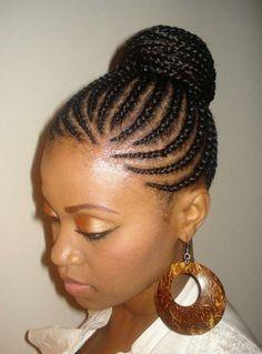 Tous les cheveux afro de cette jeune femme ont été coiffés en petites tresses plaquées sur sa tête et se dirigeant vers le haut arrière de celle-ci. Le coiffeur a ensuite assemblé toutes les tresses et les a tournées pour former un beau chignon.