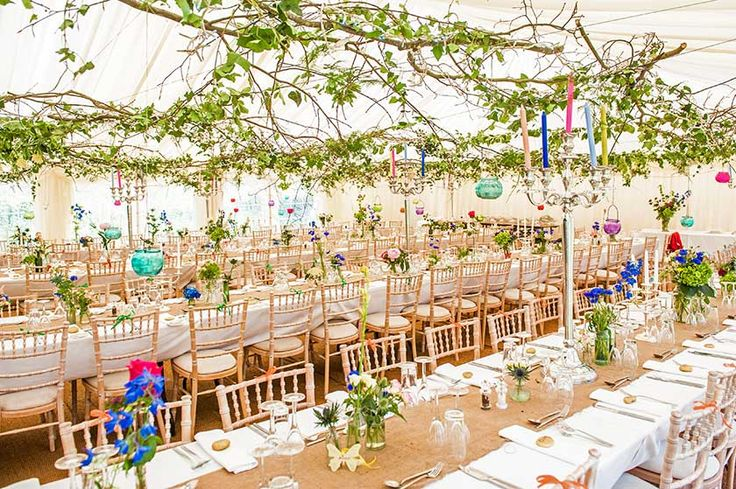 Vintage wedding tent - the unusual feature here is branches and leaves supported by wires on the tent roof. Little glass containers - bright dots of colour - could then be hung from the branches.