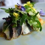 Gegrilde sardines met een salade van tomaten, gerookte schapenkaas en basilicum