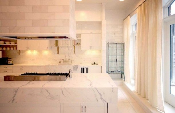 Gwyneth Paltrow's loft-kitchen - The kitchen features lots of white marble, but it also has long, flowy white curtains framing the floor-to-ceiling windows that soften things up a bit.