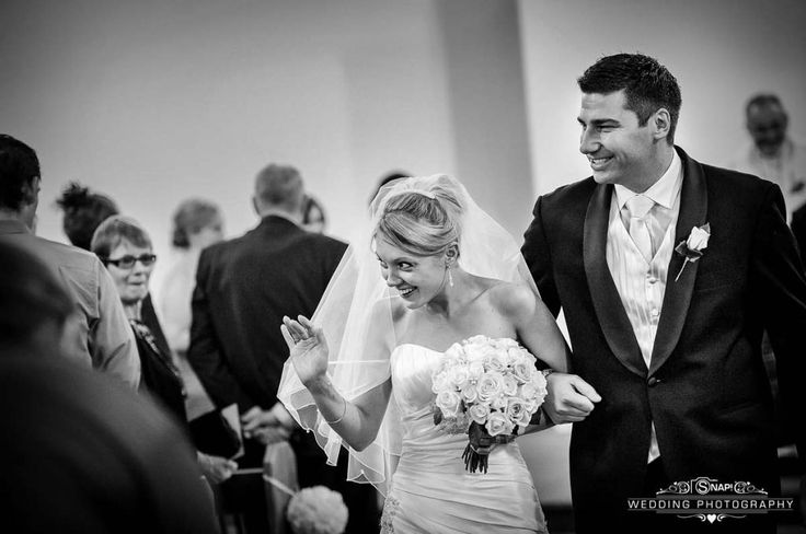 Cute wave from bride during the recessional. More wedding photography by Anthony Turnham at www.snapweddingphotography.co.nz