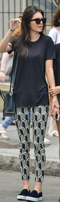 Black leather handbag, white print pants, and sneakers