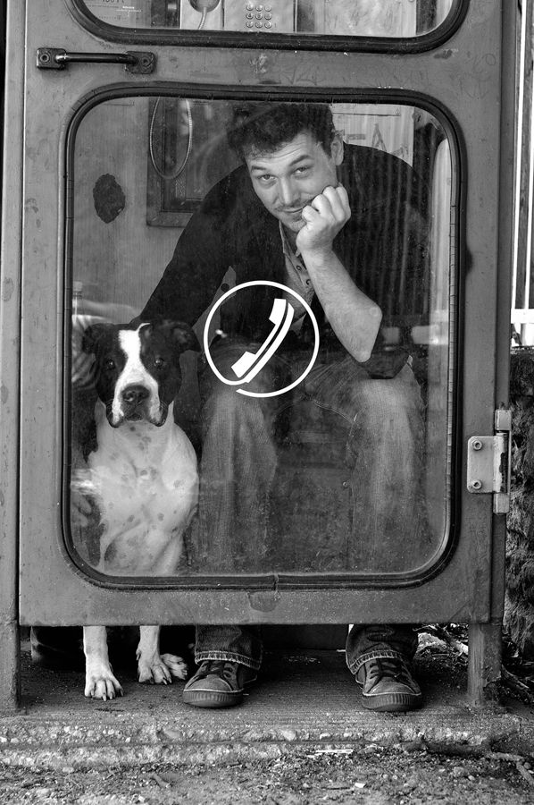 man in a phone booth with a dog