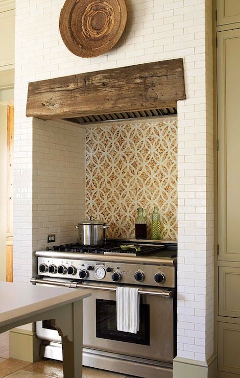 Gorgeous kitchen with cooking nook featuring African basket on Walker Zanger Gramercy Park Heirloom White Tile over re-claimed wood kitchen hood paired with Ann Sacks Custom Interlocking Ovals Tiles by Erin Adams over Thermador Range over limestone floor.