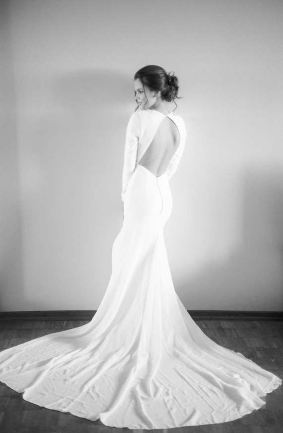 5e833c7941a5 This wedding dress is about elegant simplicity and modern minimalist  silhouette. It features open back cut, delicate buttons, long sleeves and  train.