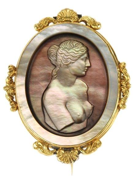 An abalone shell cameo brooch, carved to depict a nude female bust, within a late 19th c. gold scrolling