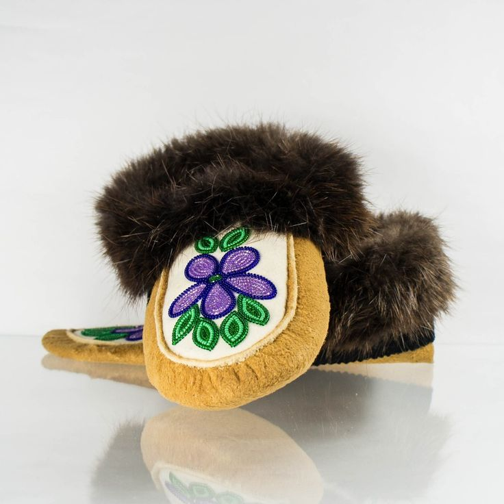 These beaded moose hide moccasins are a genuine piece of Aboriginal artwork, featuring hand-tanned moosehide, beaver fur trim and a white stroud upper with beautiful purple and green beadwork.