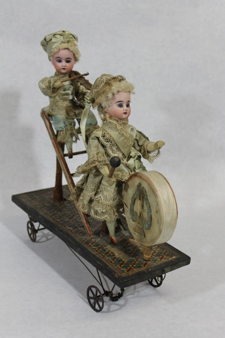 """Authentic Antique Mechanical French Bisque Dolls Drum, Violin Automaton Pull Toy.……The two small French Bisque Head Dolls in this auction measure 7 ½"""" tall and have hand painted faces, paperweight glass eyes, and their original hair and clothing. The young boy is playing a violin, while the young girl beats a drum.  Circa 1900    Sold ebay 1575.00"""