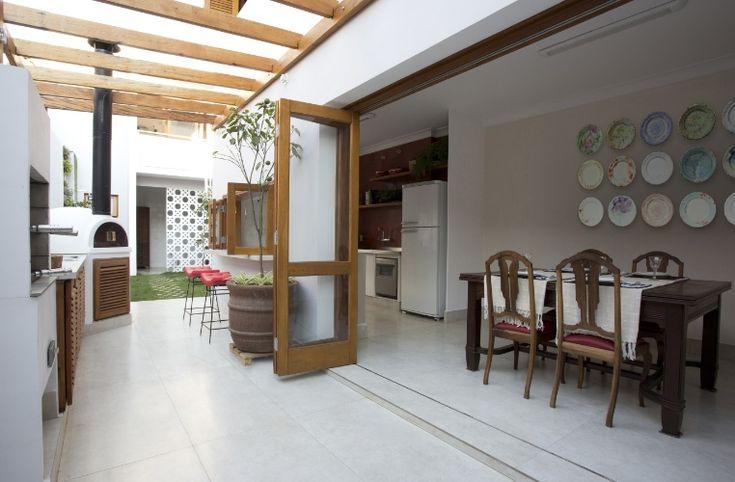 """DEPOIS - A cozinha (à dir.) é integrada ao espaço gourmet por portas articuladas (camarão): o novo ambiente ocupa o espaço da antiga lavanderia (corredor lateral) e se tornou uma área de lazer e de recepção da casa, com churrasqueira e forno de pizza, além de um pergolado em madeira de demolição. O projeto do escritório SET Arquitetura orientou o """"retrofit"""" do sobrado na região central de São Paulo, originalmente construído nos anos 1950"""