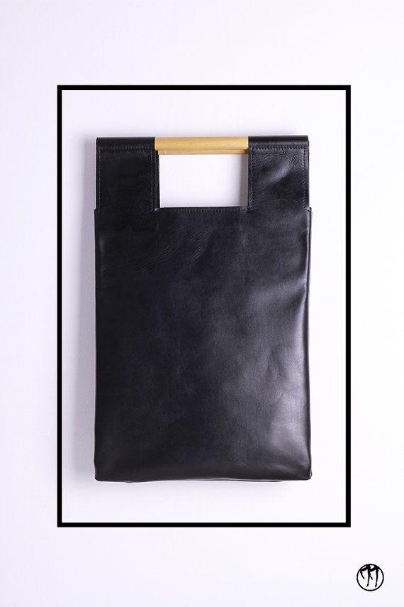 Pelle nera di prima qualità. Manici in legno di faggio con rifinitura satinata.  Doppia tasca interna e laccio portachiavi interno con moschettone.