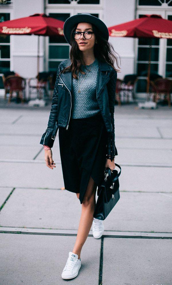 Street style look com saia social, jaqueta preta, sueter, tenis branco e chapéu.