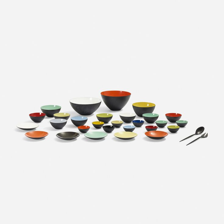 Lot 164: Herbert Krenchel. Krenit bowls, set of twenty-eight. 1953, enameled steel. 9¾ dia x 5½ h in. estimate: $2,000–3,000. Collection includes twenty-eight bowls of varying sizes and two serving utensils, 30 pieces total. Signed with cast manufacturer's mark to each server: [Krenchel Denmark].Signed with stamped manufacturer's mark to underside of eight examples: [K Krenit Denmark].